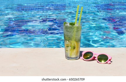 Poolside cocktail served cold at pool bar with Mojito and pink sunglasses at sunny summer day.