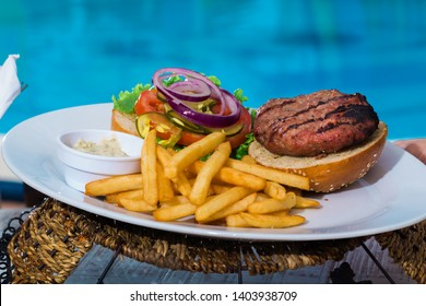 Poolside hamburger with ingredients showing, with fries on the side and clear blue pool behind.