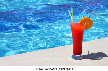 Poolside red cocktail served cold at pool bar at sunny summer day. Summer holidays, travel, people and vacation concept.