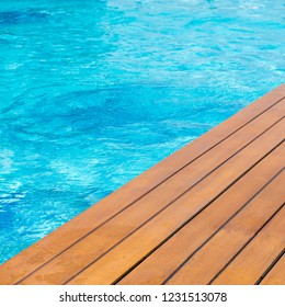 Poolside at resort with wooden decking.