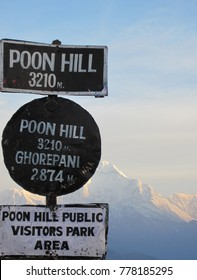Poon Hill visitor park sign with snowy mountains in the background on a cold winter morning.