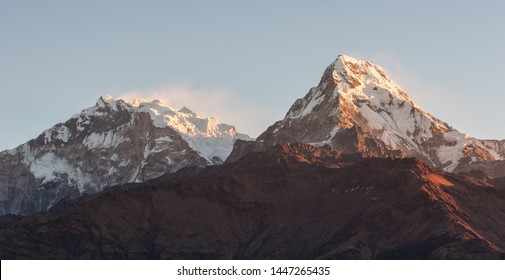 Poonhill view of Annapurnas. Warm pink and orange sunrise light over Annapurna mountain range with blue sky and beautiful clouds, view from Poon hill in Himalayas, Nepal. Annapurna one and Annapurna