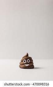 Poop emoticon on bright background. Minimal concept.