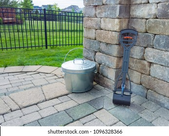 Pooper scooper and metal bucket in a garden neatly stored on an exterior patio ready for collecting dog faeces from the family pet
