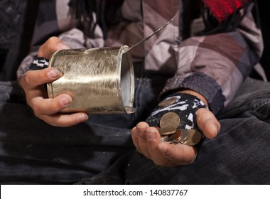 Poor beggar child counting coins - closeup on dirty hands holding tin can