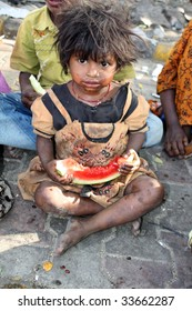 A poor beggar girl from India eating a watermelon.