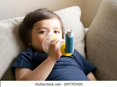 Poor boy have a problem with chest coughing holding inhaler mask, Child using the volumtic for breathing treatment, Kid having asthma allergy using the asthma inhaler, Healthcare and medicine concept