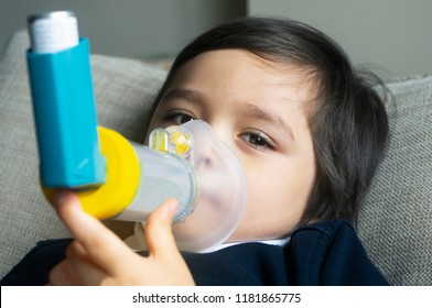 Poor boy have a problem with chest coughing holding inhaler mask,Child using the volumtic for breathing treatment,Kid having asthma allergy using the asthma inhaler,Healthcare and medicine concept