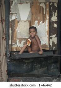 a poor boy holding bread posin in a slum in mumbai