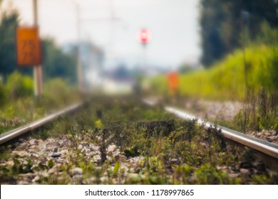 Poor condition mainline train tracks. Heavy gauge normal train tracks with wooden sleepers with grass growing between gravel due to poor maintenance of infrastructure. Photo with an old vintage lens