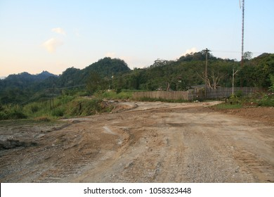 poor condition Rural road in Thailand. It's a dirt road to forest and countryside village in raining season