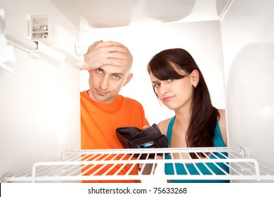 Poor couple with empty wallet looking in bare interior of empty modern refrigerator.