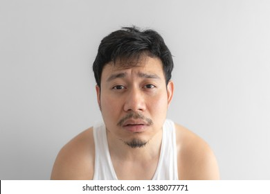 Poor and depressed Asian man wear white tank top on grey background. Concept of desperate life.