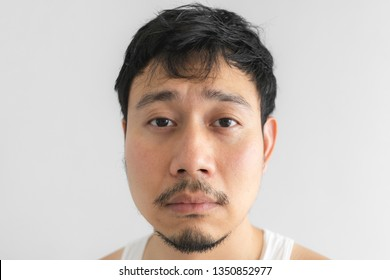 Poor and depressed face of Asian man on grey background. Concept of desperate life.