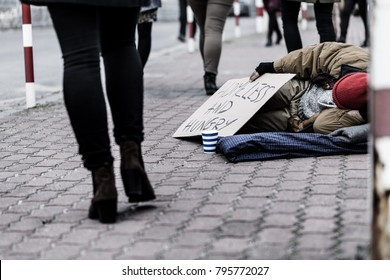 Poor and dirty person lying on the sidewalk next to pedestrians. Problem of poverty in the city