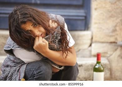 poor drunk woman sitting on sidewalk with bottle of wine