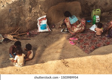 A poor family of six people living on the floor at the roadside with bare essentials. Mother prepares food for all with wood fire. Scene showcasing poverty in India.