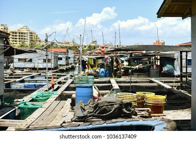 Poor fishing village on water. Many junk. Rich city in background. Asian country. Sunny day