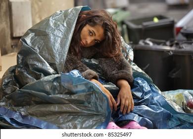 poor girl in city sitting in street near bin