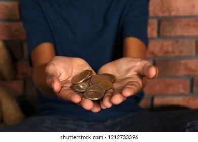 Poor homeless boy begging near brick wall, focus on hands