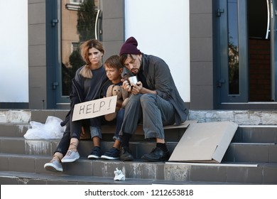 Poor homeless family begging and asking for help on city street