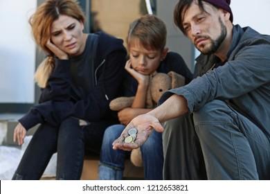 Poor homeless family begging on city street