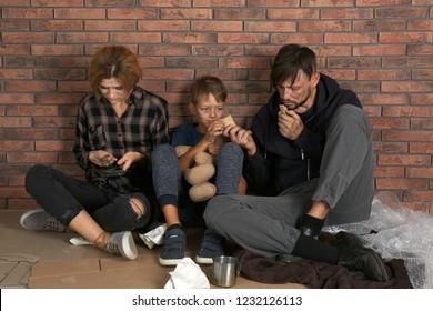 Poor homeless family sitting on floor near brick wall