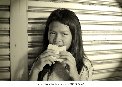 Poor homeless girl eating a sandwich standing against a closed shop