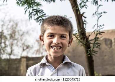 a poor homeless happy smiling orphan child
