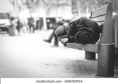 Poor homeless man or refugee sleeping on the wooden bench on the urban street in the city, social documentary concept, selective focus, black and white