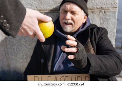 Poor homeless man taking apple