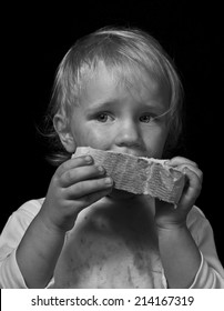 poor hungry child eating bread, black and white portrait on black
