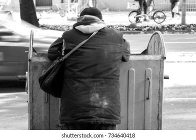 Poor and hungry homeless man in dirty clothes looking for food in the dumpster on the urban street in the city black and white