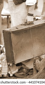 poor immigrant with old leather suitcase waiting to boarding sepia effect