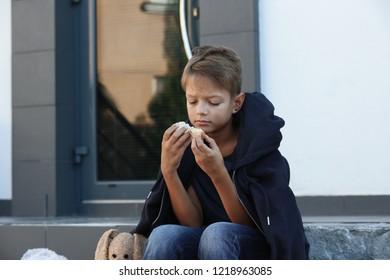 Poor little boy with bread on city street