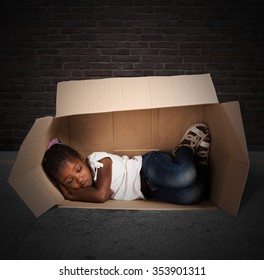 Poor little girl sleeps in a cardboard