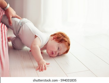 Poor little toddler baby fell down from the bed while crawling on it. Dad missed to catch him