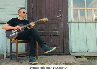 A poor lonely guitarist sits by the porch of an old house, plays bass guitar and sings.