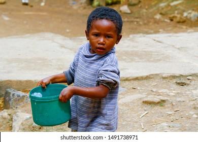 Poor malagasy boy carrying plastic bucket - poverty