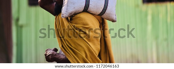 Poor man carrying a white bag on his shoulder isolated unique photo