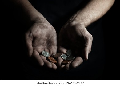 Poor man with coins on dark background, closeup