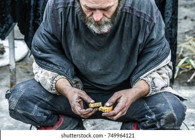 poor man homeless with  dirty hands  eating piece of bread in modern capitalism society