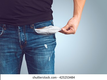 Poor man in jeans with empty pocket
