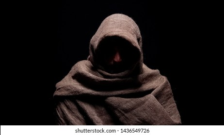 Poor man in rough robe looking down with humility, early christian prophet