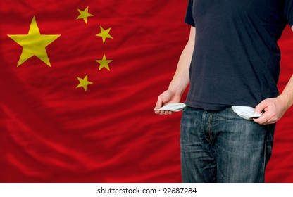 poor man showing empty pockets in front of china flag