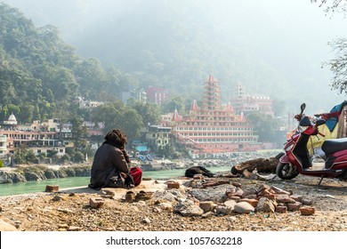 poor man sits on the banks of the Ganges river and looks towards the temple Tera Manzil Temple. Morning prayer before the Holy place. Meditation in Rishikesh. social inequality, social stratification