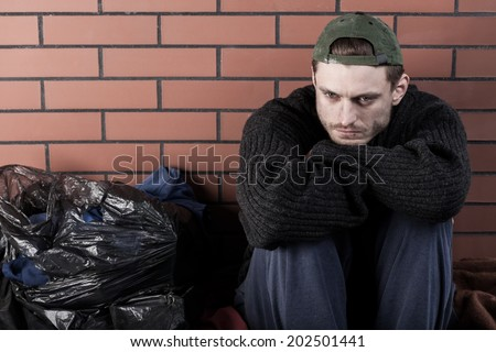 Poor Man Sitting Hunched On Ground Stock Photo Edit Now 202501441