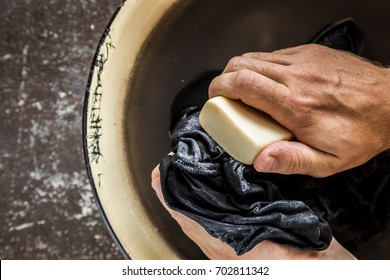 Poor man's hands washing dirty clothes in the old metallic bowl. Poverty concept. Clothes care. Rural life.