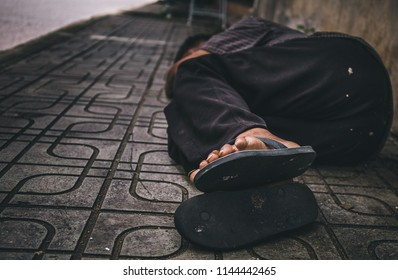 poor old man or beggar begging you for help sleep in dirty slum at sideroad. concept for poverty or hunger people,human Rights,donate and charity,background text.