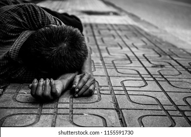 poor old man or beggar begging you for help sleeping sideroad at dirty slum. concept for poverty or hunger people,human Rights,donate and charity,background text.black and white tone.